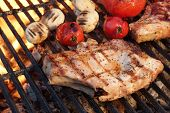pic of rib eye steak  - Pork Rib Steaks Tomato And Mushrooms On Hot Flaming BBQ Charcoal Grill - JPG