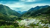stock photo of ifugao  - Amazing panorama view of rice terraces fields in Ifugao province mountains under cloudy blue sky - JPG