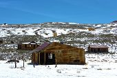 stock photo of collapse  - Collapsing wooden homes amongst snow and sagebrush taken at the historic mining town of Bodie - JPG
