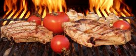 image of charcoal  - Pork Rib Steaks Tomato And Mushrooms On Hot Flaming BBQ Charcoal Grill - JPG