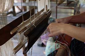 picture of handloom  - Woman weaving silk in traditional way at manual loom - JPG