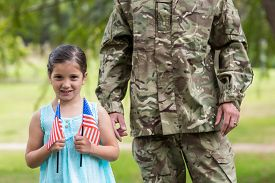 stock photo of reunited  - Soldier reunited with his daughter on a sunny day - JPG