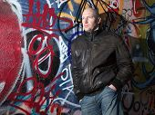 picture of deprivation  - man with attitude in front of graffiti wall in urban area - JPG