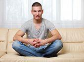 handsome man sitting yoga-pose at home
