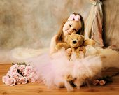 stock photo of ballerina  - Adorable little girl dressed as a ballerina in a tutu hugging a teddy bear sitting next to pink roses - JPG