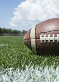 Closeup photo of a football resting on an outdoor field poster