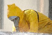 pic of decontamination  - man in a yellow chemical protection suit running in the rain - JPG