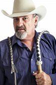 Old cowboy with a bullwhip