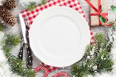Christmas dinner table setting with fir tree, gift box. Top view with copy space poster