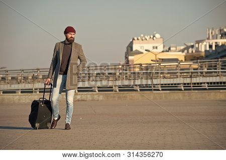 poster of Hipster Ready Enjoy Travel. Carry Travel Bag. Man Bearded Hipster Travel With Luggage Bag On Wheels.