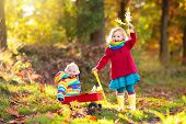 Mother And Kids Play In Autumn Park. Mom And Child With Umbrella And Rain Boots Play Outdoors In Rai poster
