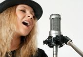 Young Woman Singing With Studio Microphone