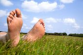 Relaxed Foot On Grass With Cloud Background
