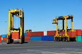 foto of straddling  - Straddle carriers carrying containers to and from a stacking area - JPG