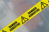 picture of unsafe  - Danger Asbestos yellow warning tape close up - JPG