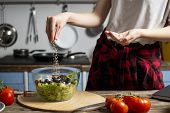 Young Cheerful Girl Prepares A Vegetarian Salad In The Kitchen, She Salts And Adds Spices, The Proce poster