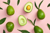 Avocado and green leaves pattern on pink background. Top View. Pop Art design, creative summer food  poster