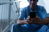 Front view of Caucasian male surgeon using mobile phone while sitting on stairs at hospital. Shot in poster