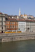 Danube Riverside In Budapest Featuring A Tram And Matyas Templom.