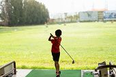 Young Asian Boy Is Practicing His Golf Swing At The Golf Driving Range. poster