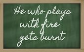 Expression -  He Who Plays With Fire Gets Burnt - Written On A School Blackboard With Chalk