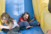 picture of inflatable slide  - Two beautiful little girls having fun on inflatable playground - JPG