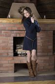 girl in blue jersey heating near red brick fireplace