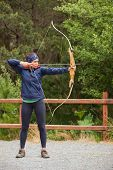 Focused brunette practicing archery at the range