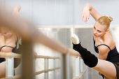 Ballerina stretches herself near barre and mirrors in the classroom