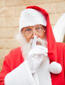 Portrait of senior man dressed as Santa Claus with finger on lips standing outdoors