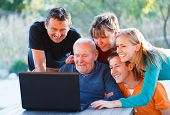 stock photo of granddaughters  - Family watching something interesting with old grandfather - JPG