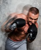 Young sporty man in boxing gloves in motion