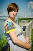 Pregnant Beautiful Young Woman By Embankment, Near The River Basking In The Sun