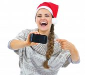 Closeup On Young Woman In Sweater And Christmas Hat Pointing On