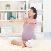 Pregnancy yoga meditation. Full length healthy 8 months pregnant calm Asian woman meditating or doing yoga exercise at home. Relaxation yoga arms stretching pose.
