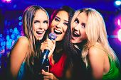 foto of karaoke  - Portrait of happy girls singing in microphone in the karaoke bar - JPG