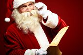 stock photo of christmas claus  - Portrait of happy Santa Claus holding Christmas letter in his hands and looking at camera - JPG
