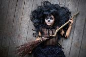 Portrait of cute girl in black wig holding broom and looking at camera