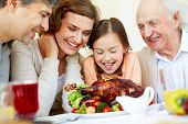 Portrait of happy family sitting at festive table and looking at roasted turkey