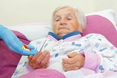 picture of hypertensive  - Elderly woman takes pills from a nurse - JPG
