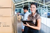 Young Asian woman in a suit with headset in a indonesian warehouse, she is from the Customer Service, a coworker standing in background