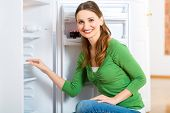 Young woman or housekeeper defrosts the refrigerator and wipes in clean