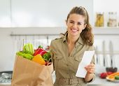 Smiling Young Housewife With Check And Shopping Bag Full Of Vege