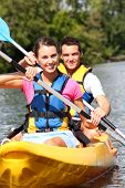 Couple riding canoe in river