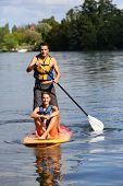 Couple riding stand-up-paddle on river