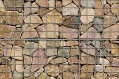 stock photo of rip-rap  - various stones carefully aranged in an iron net to make a wall - JPG