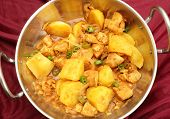 A vindaloo chicken and potato curry, cooked balti-style in a kadai (karahi) cooking pot, garnished w
