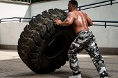 picture of strongman  - Muscular Man with Truck Tire doing crossfit style workout turning tire over - JPG