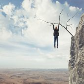 image of dangerous situation  - Business man climbs a mountain - JPG