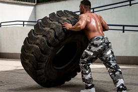 foto of strongman  - Muscular Man with Truck Tire doing style workout turning tire over - JPG